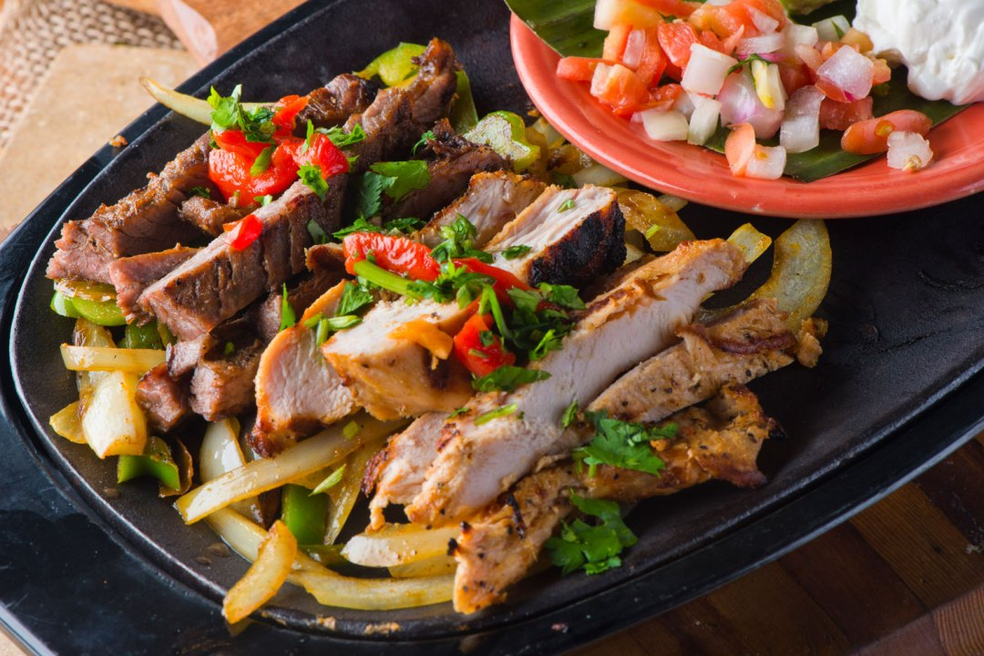 Grilled strips of chicken and steak are laying on a bed of fried onions and peppers with cilantro placed on top. A small bowl of diced tomatoes and onions sits next to it.