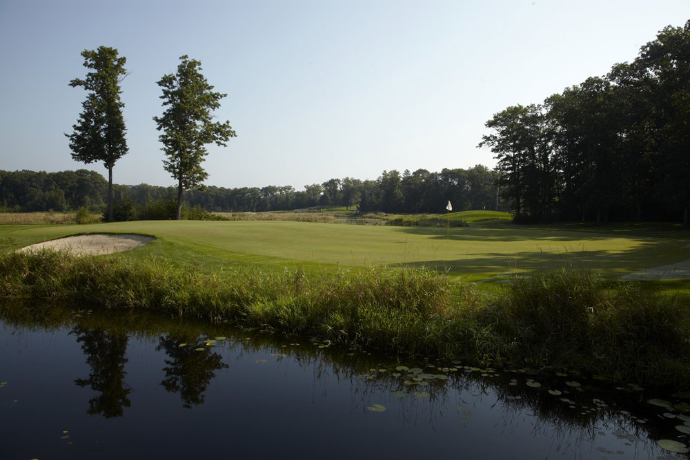 A picture of a golf course with a sand trap and pond early in the morning.
