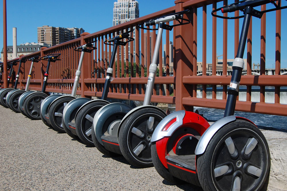 A row of empty segways lined up against a railing.