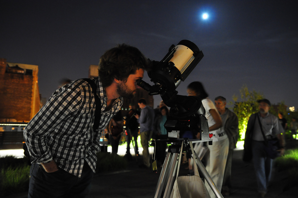 People taking turns viewing through a telescope pointed at the night sky.