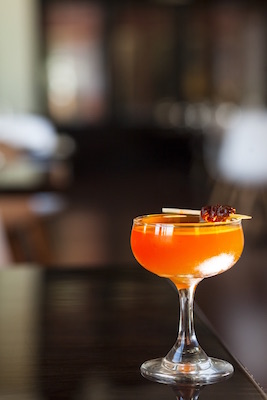 Orange cocktail in a small martini glass with three small cherries on a toothpick as a garnish.
