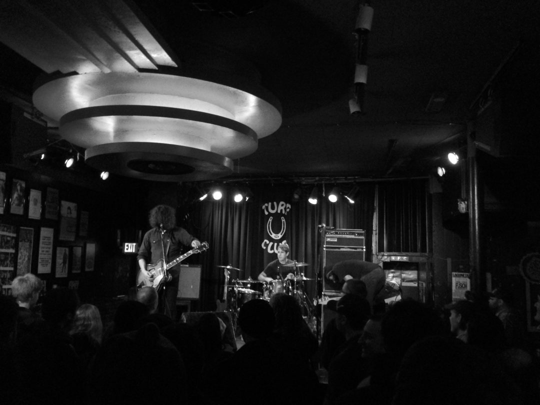 Black and white photo of a band playing live music at a bar.