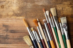 Different sized paintbrushes laying on a wooden table.
