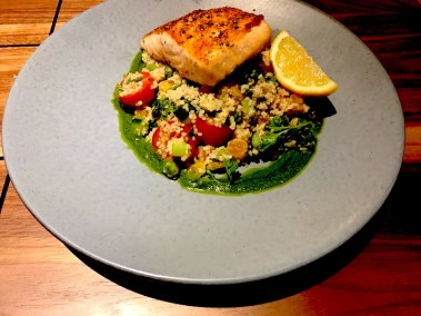 Plancha-cooked salmon on a bed of tabbouleh salad.