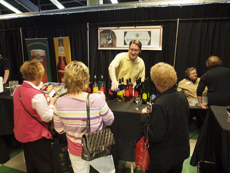 Three women getting glasses of wine from a vendor at a wine tasting event.