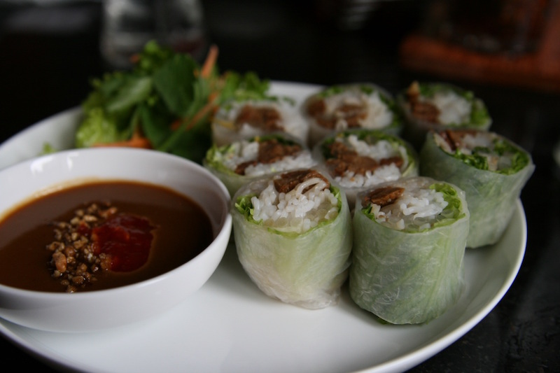 Mock duck spring rolls next to a bowl of brown sauce at a Vietnamese restaurant.