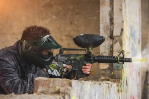 Paintball player in protective uniform shooting target with gun