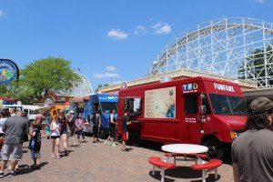 People milling around two food trucks at an outdoor amusement park on a clear summer day