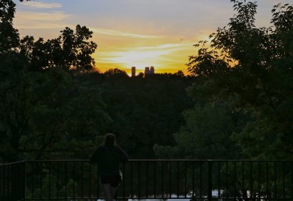 Photo of girl leaning against railing watching sunset over downtown Minneapolis from The Monument.