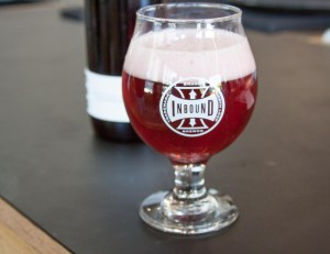 Tulip beer glass with a reddish beer sitting on a counter at Inbound BrewCo's taproom in North Loop.