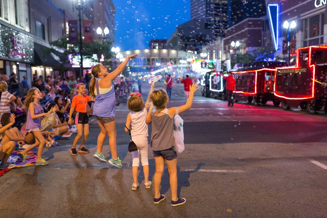 Kids enjoying the CenterPoint Energy Parade at the Minneapolis Aquatennial.
