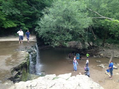 Families play at the bottom of the waterfall while two men look at the view from on top of it in Nerstrand Big Woods State Park.