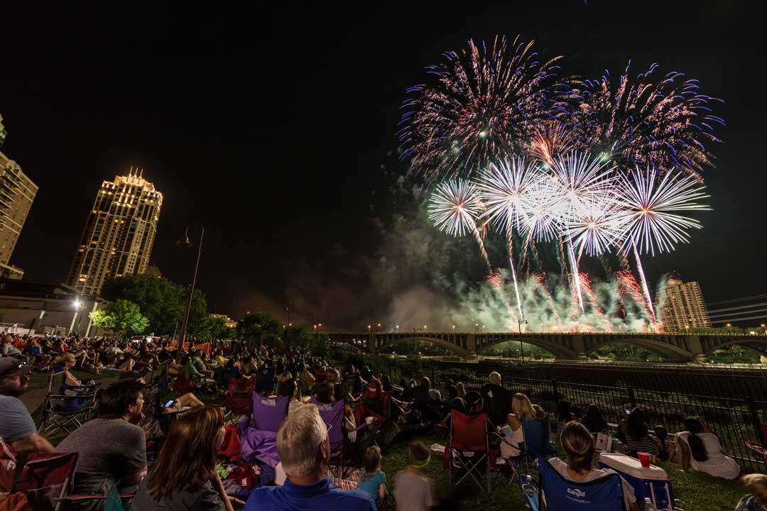 A crowd of people enjoying the Minneapolis Aquatennial Target Fireworks show.