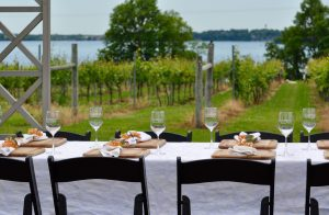 Outdoor table with wine glasses in front of vineyards and lake at The Winery at Sovereign State in Waconia