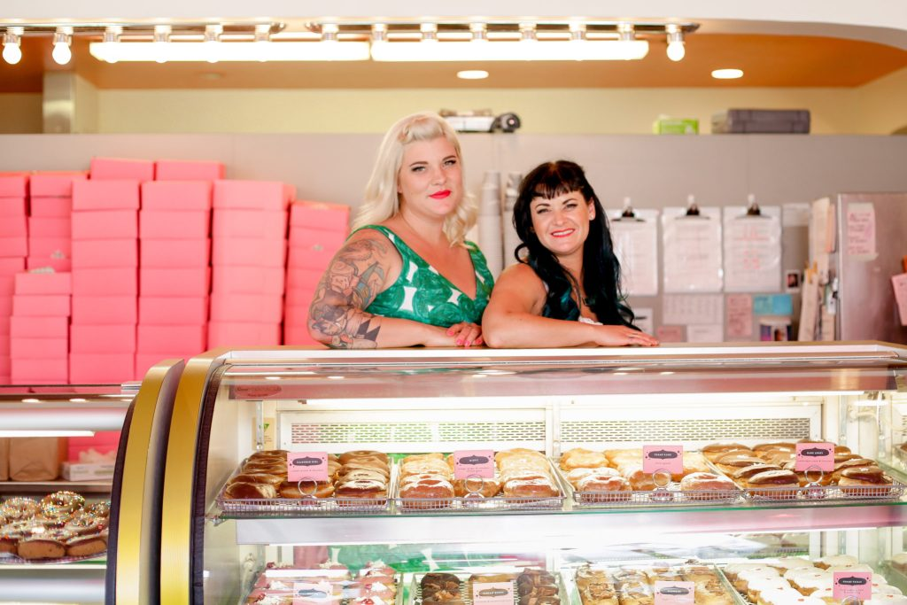 Teresa Fox and Arwyn Birch stand behind their doughnut display case.