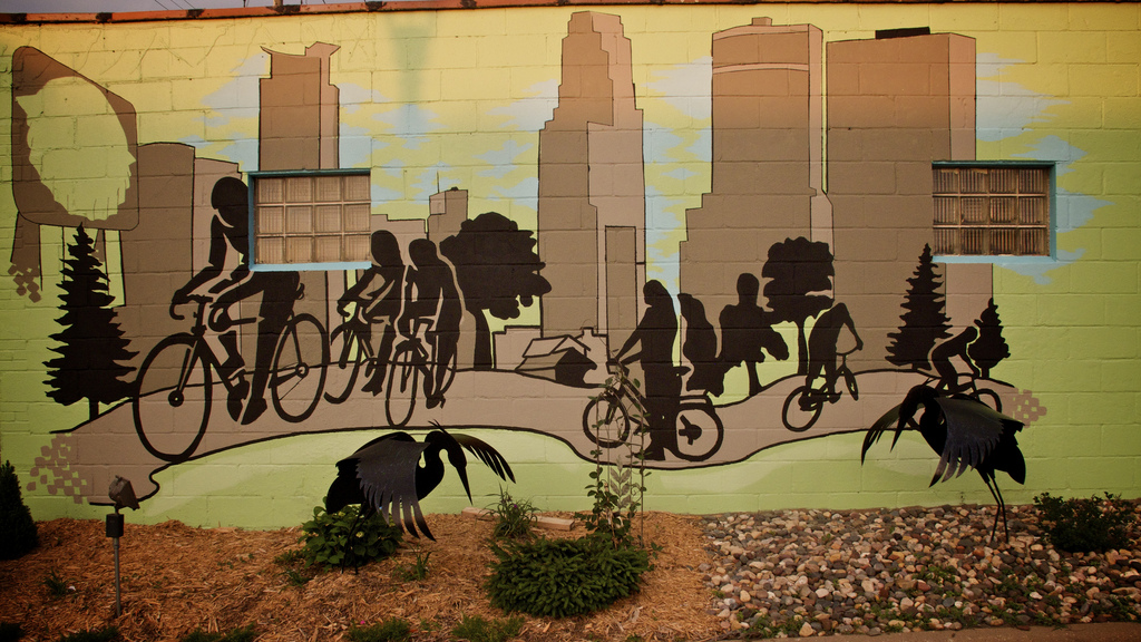 Photo by Bjorn/flickr. Bicyclists on a city path with the Minneapolis skyline in the background. A nice 3D touch is added with the metal birds in front of it.