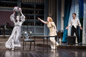 Photo by Dan Norman. Elia Monte-Brown (Elvira), Heidi Armbruster (Ruth) and Quinn Mattfeld (Charles Condomine) in the Guthrie Theater's production of Blithe Spirit by Noël Coward, directed by David Ivers. Scenic design by Jo Winiarski, costume design by Meg Neville, lighting design by Xavier Pierce. November 25, 2017 – January 14, 2018 on the McGuire Proscenium Stage at the Guthrie Theater, Minneapolis.
