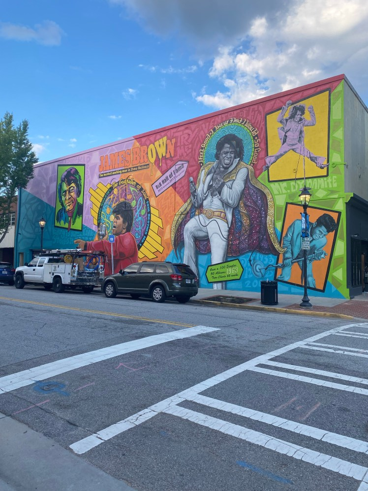 Street corner. Colorful mural featuring various images of James Brown.