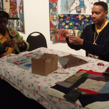 A man and a woman working on quilts