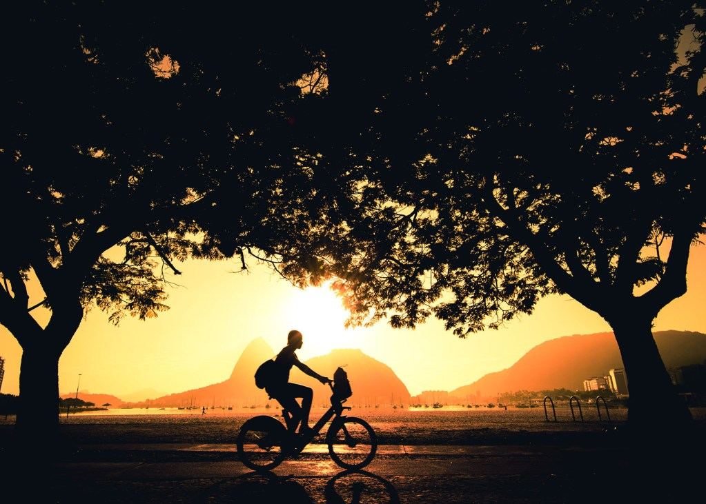 Woman cycling in the morning and the Sugarloaf Mountain is in the horizon, in Rio de Janeiro, Brazil.