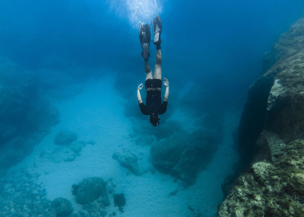A DSLR Canon underwater photo of a Brazilian man enjoying his vacation at tropical island Fernando de Noronha, Brazil. He is free diving wearing snorkeling equipment in clear blue water at Sancho Beach (Praia do Sancho), which has been considered the most beautiful beach in the world.