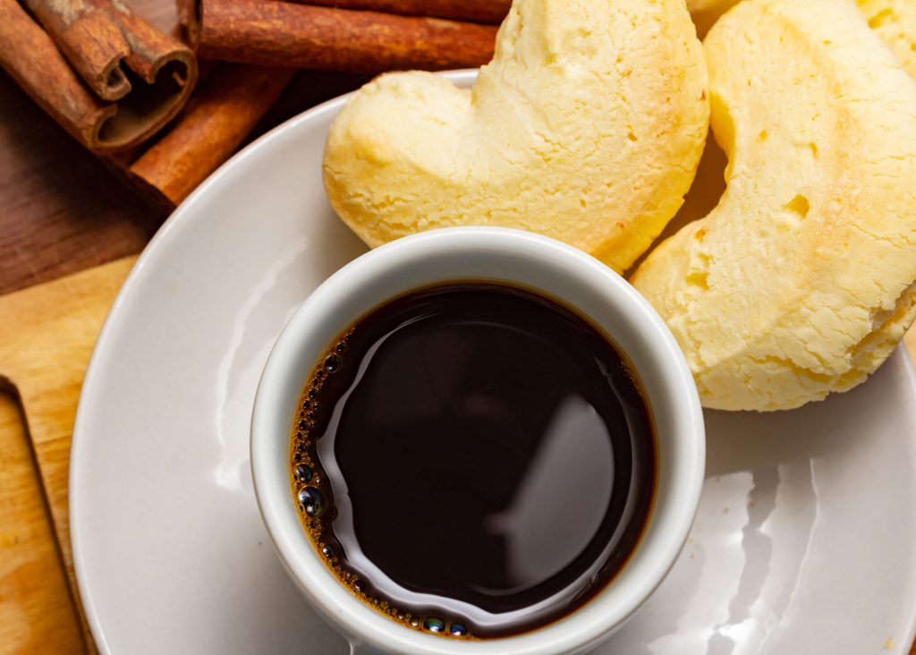 Goiania, Goias, Brazil – February 19, 2021: Cup of coffee with cheese biscuit on a wooden board with pieces of cinnamon.