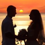 Shape of a bride and groom on the beach at sunrise time