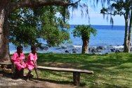 Deux petites filles regardant la mer dans leur robe rose, couleur choisie par Paama pour représenter l'île durant le regroupement national annuel Presbytérien qui s'est tenu pour la première fois à Paama cette année là.