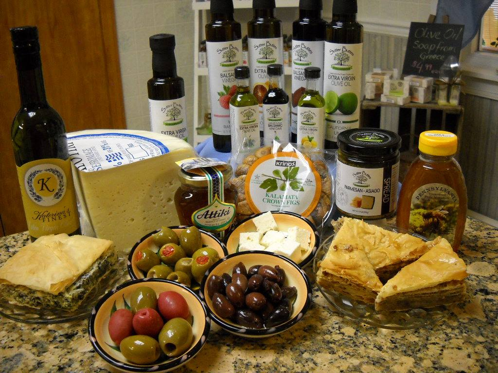 an assortment of greek food including olive oils, olives, baklava, cheese, and honey