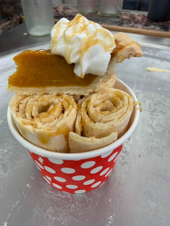 rolled ice cream in a cup with a piece of pumpkin pie on top