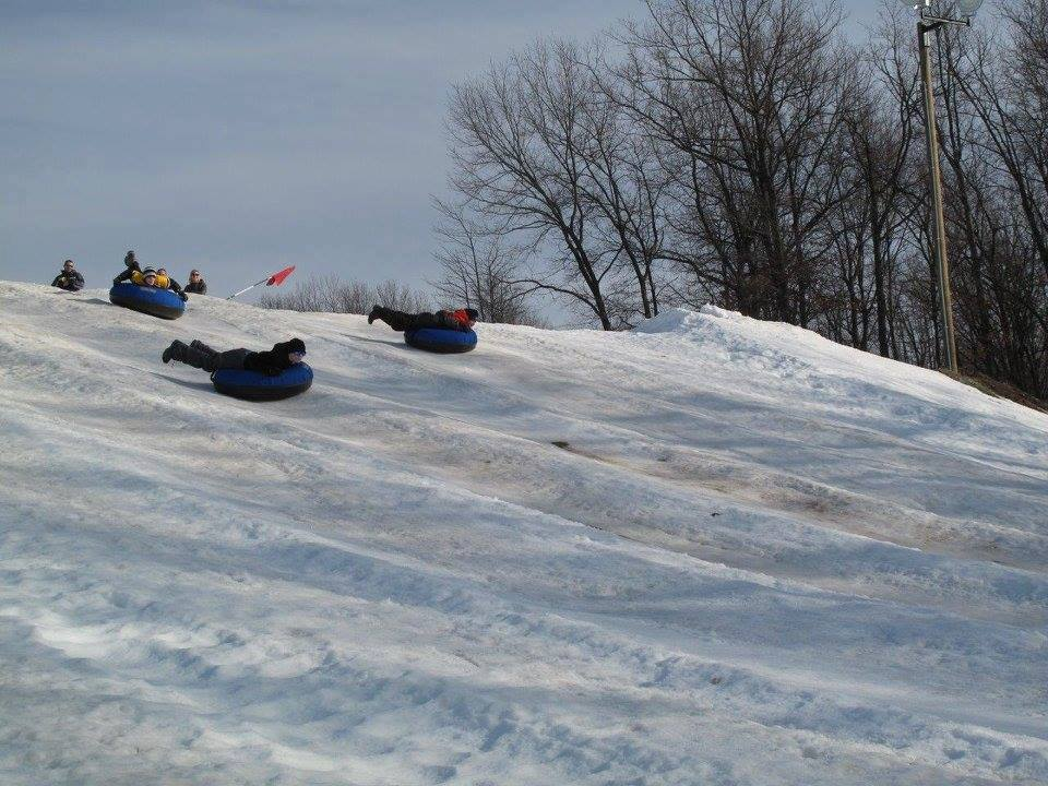 children tubing down a snowy hill