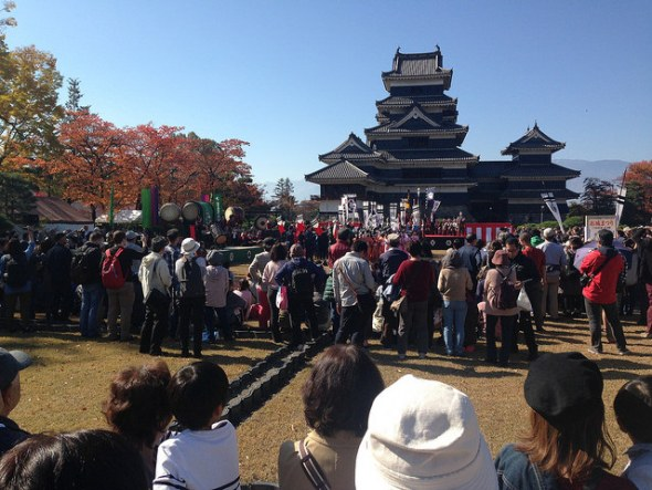 Crowd and samurai parade participants gathered at Matsumoto Castle for the official festival kick-off ceremony