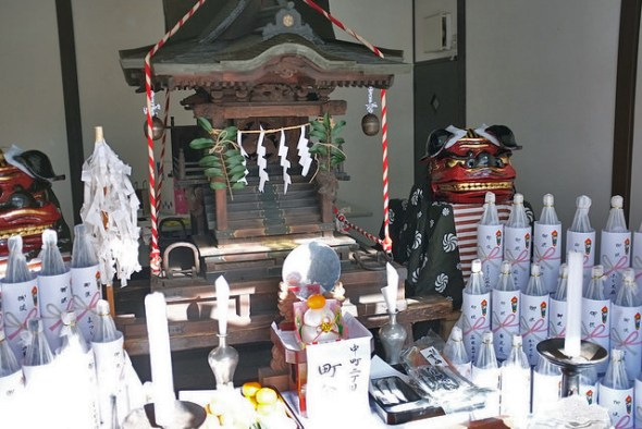 "The mikoshi set up as an altar in Nakamachi surrounded by sake and the ""shishimai"" lion dance costumes"