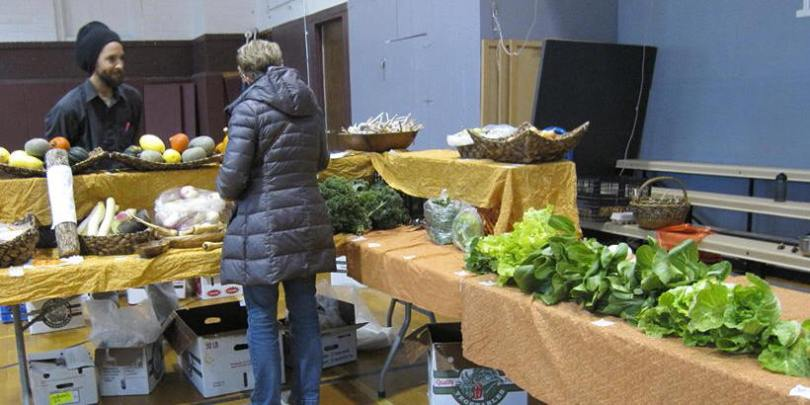Produce tables and attendees at the Mount Vernon Indoor Winter Farmers' Market