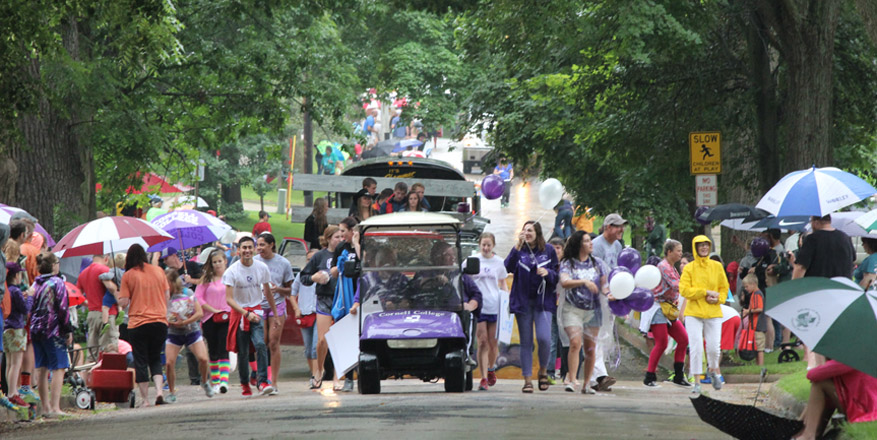 Paraders walk down a tree-lined street.