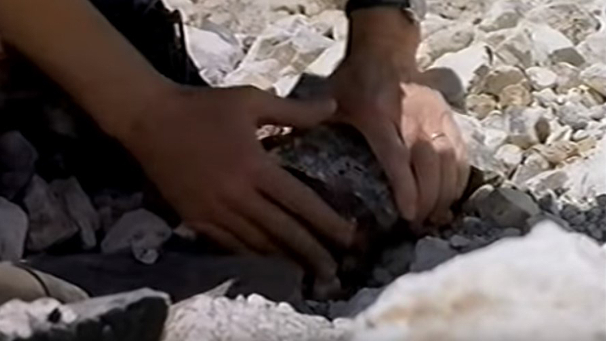 Scene from film Meteorites (1998) picking up a rock from a crater. In blog about asteroid and comet impacts on Earth.
