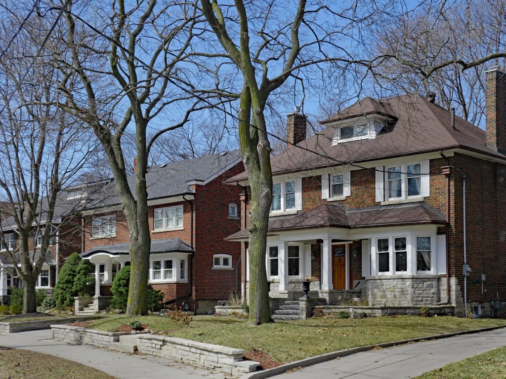 Two older red brick Toronto houses with mature trees in front tree inspection report