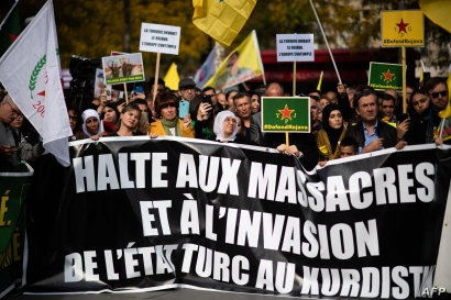 People hold pro-Kurd flags and banner in Paris on October 12, 2019 during a demonstration to support Kurdish militants and…