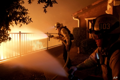 In this Thursday, Oct. 10, 2019 photo, Los Angeles City firefighters battle the Saddleridge fire near homes in Sylmar, Calif. …