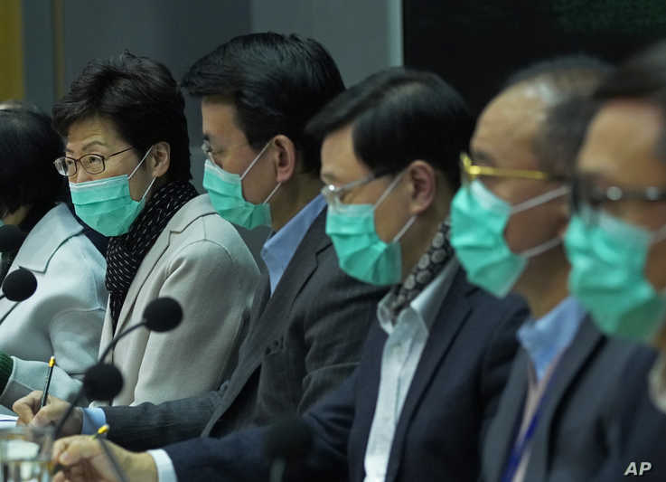 Hong Kong Chief Executive Carrie Lam, left, wears a protective face mask speaks during a press conference held in Hong Kong,…