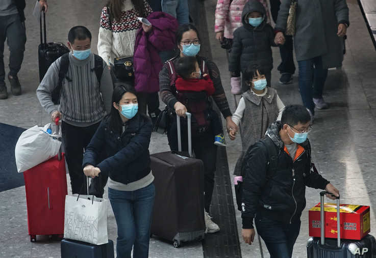 Passengers wear protective face masks arrive at the high speed train station in Hong Kong, Tuesday, Jan. 28, 2020. Hong Kong's…