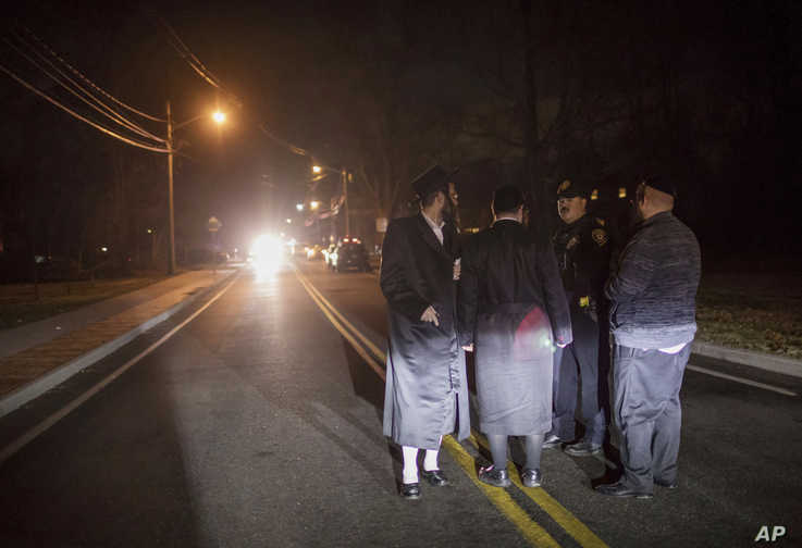 Orthodox Jews talk to a police officer near the scene of a stabbing that occurred late Saturday during a Hanukkah celebration, in Monsey, New York, Dec. 29, 2019.