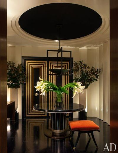 A surprising pop of orange in a fantastic art deco foyer makes the room