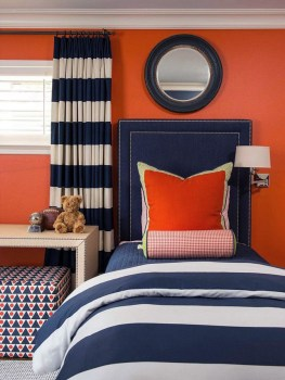 Bold orange walls with navy blue are perfect for a boys room
