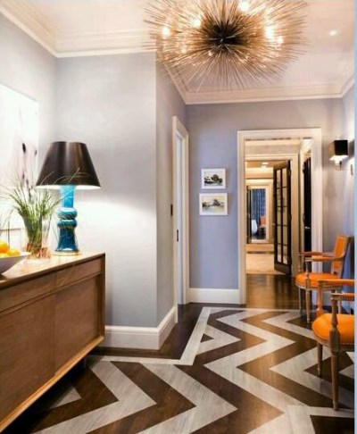 Choosing a soft wall color and using a pair of subtle warm orange chairs with a teal blue lamp add a fresh pop to this hallway