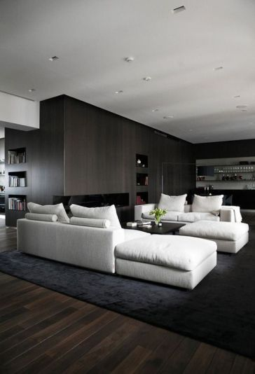 Tasteful, masculine and clean arrangement of this pair of sectional sofas and ottomans in white on black. Very chic and comfortable for entertaining and conversation.