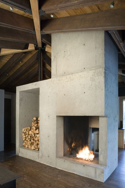 A minimalist poured concrete fireplace creates an unpretentious clean ambiance in this cozy cabin.