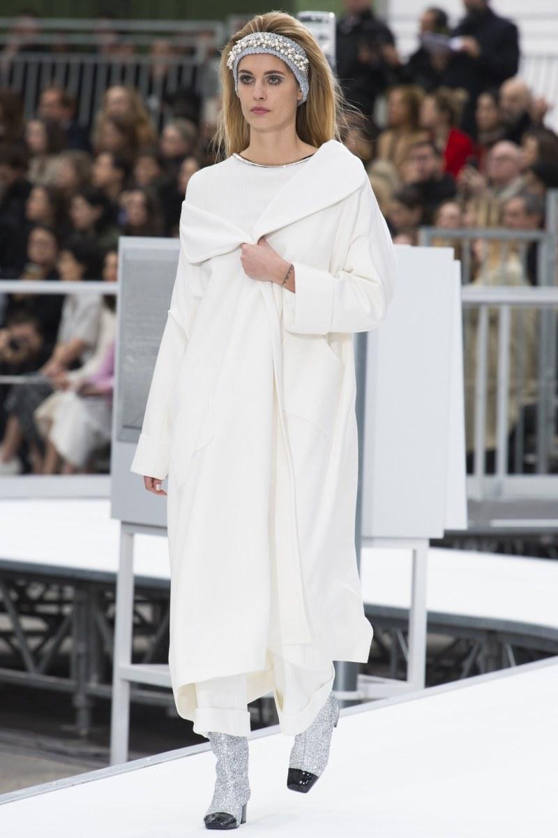 model wearing white coat walks down runway at chanel show