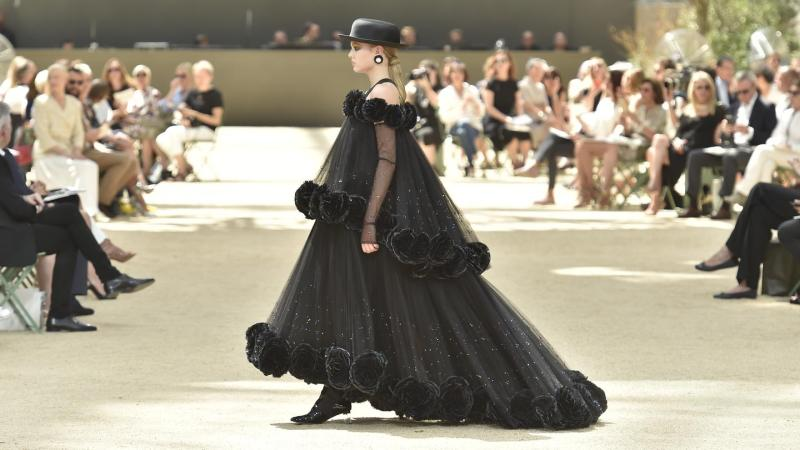 model walks down runway in black chanel gown during paris couture fashion week