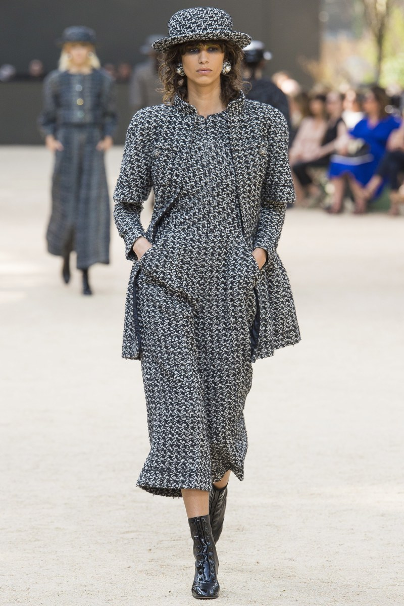 Model walking down runway at Chanel fall 2017 couture show in one piece jumpsuit and coat
